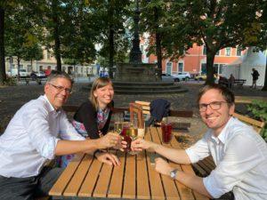 Bild zeigt die 3 Gründer*innen von Vertragswerk an einem Tisch, wie sie mit einem Getränk anstoßen